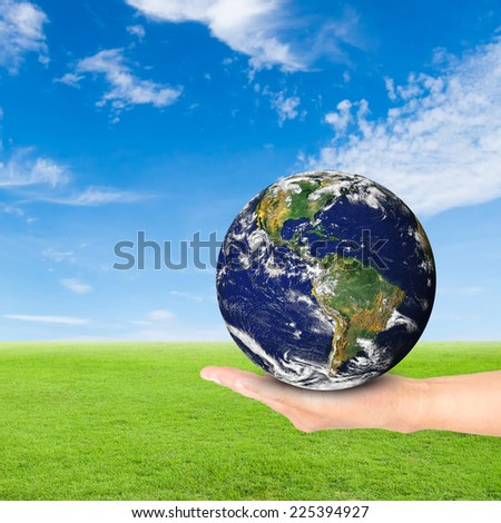 Green Earth concept,hand holding earth against green field and blue sky background.Elements of this image furnished by NASA