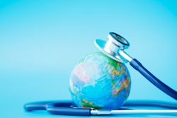 Green Earth day, Save the wold and Global healthcare concept. Stethoscope wrapped around globe on blue background.
