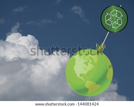 Green earth recycling sign against a cloudy blue sky