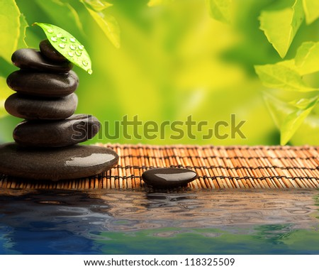 green eco background with spa stones and leaves with water and sunlight
