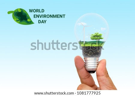 Green eco energy concept. Wind turbine and tree growing inside light bulb. nature background. Think green and Ecological concept. world environment day. #1081777925