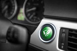 Green ECO mode button on a dashboard of a sportive car.