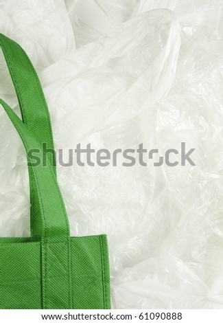 Green, eco shopping bag contrasting against disposable plastic bags.
