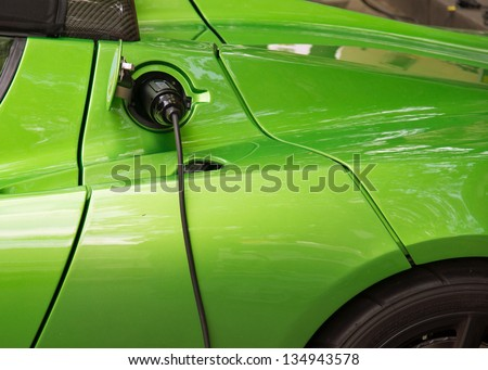 Green electric car charging Close-up of indistinguishable electric car fueling i.e plugged to the electricity hose charging battery