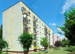 Green elevation and colorful facade of block of flats in housing estate. Urban landscape of housing blocks with laundry on balconies, Poland