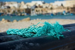 Green emerald knot isolated on fishing boat with blurry colorful village Marsaxlokk in the background. Fishing equipment, details close up.