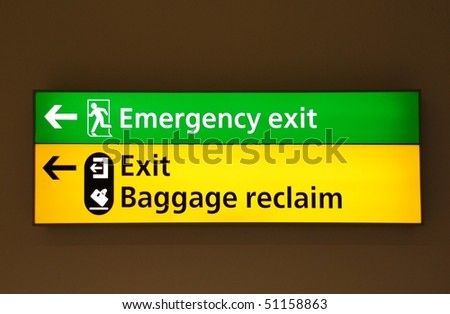 green emergency exit and yellow exit/baggage claim sign at a international airport