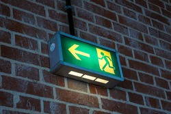Green emergency exit sign mounted on a brick wall.