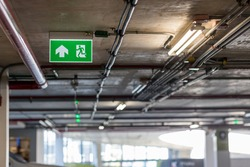 Green emergency exit sign showing the way to escape.Fire exit in the building.