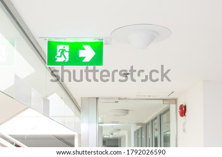 Green emergency fire exit sign or fire escape with the doorway in the building Ideas for evacuation drills in the event of a fire.
