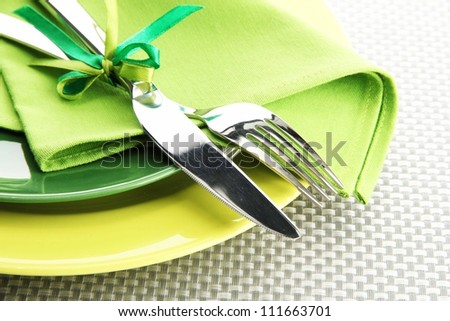 Green empty plates with fork and knife on a grey tablecloth