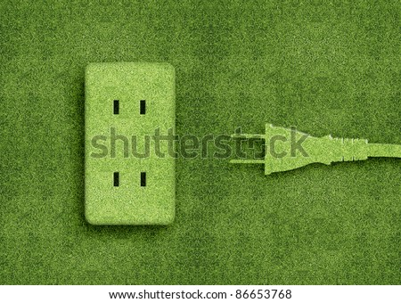 Green energy concept, Green power cord in electric outlet on a green grassland. - stock photo