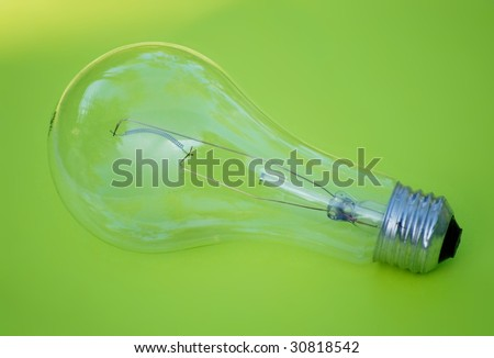 Green energy concept - un-powered incandescent light bulb on green background. The bulb is clear, not frosted. The filament is intact. The green background has a bright spot in the upper left corner.