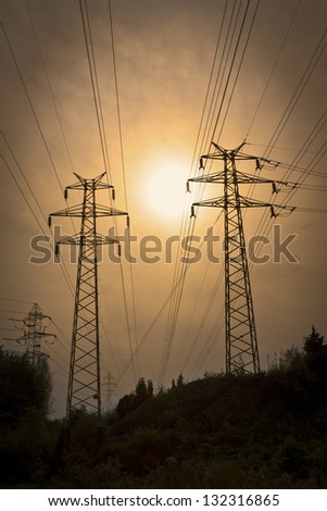 Green Energy: Electric power lines in the sunset. Electricity pylons and lines in the forest.