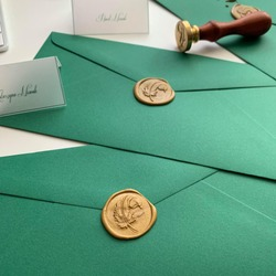 Green envelope sealed with a gold stamp