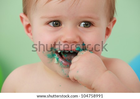 green eyed boy smiling with his hand in his mouth, with his hand and face covered in green icing and cake. with a blue balloon in the background on a green backdrop.