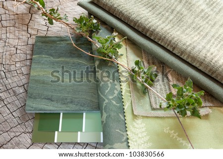 Green fabric swatches with paint color sample cards and a natural stone tile - stock photo
