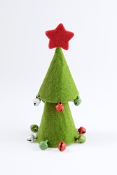 Green felt christmas tree with jingle bells against white background. Copy space.