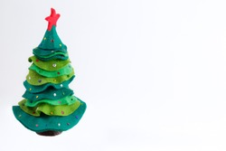 Green felt christmas tree with jingle bells against white background with copy space