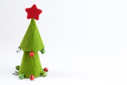 Green felt christmas tree with jingle bells against white background with copy space. Copy space.