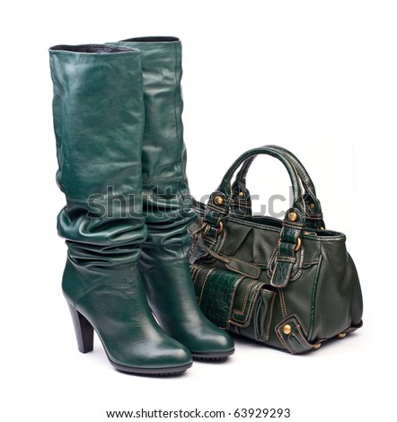 Green female high-heeled boots and leather bag on the white background