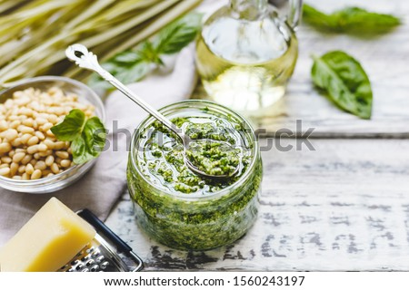 Green fettuccine and Pesto sauce in vintage spoon on glass jar of pesto sauce with ingredients on rustic white wooden table. Traditional Italian pesto recipe for making fettuccine, pasta, bruschetta. Zdjęcia stock ©