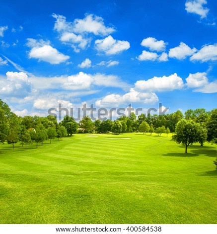 Green field and blue cloudy sky. Golf course. Fairway. European landscape