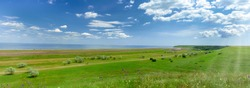 Green field and blue sky. Beautiful bright colorful summer spring landscape of green hills and sea. Panorama