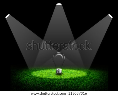Green field and lightbulb under spotlight background