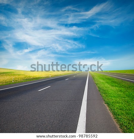 green field and road over blue sky #98785592