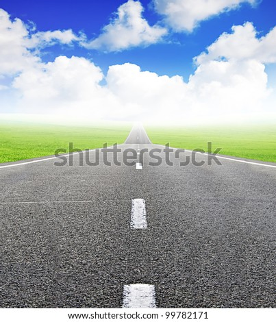 green field and road over blue sky - travel and tranportation concept