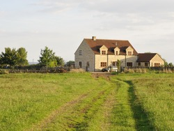 Green Field Country Lane Leading to a Farmhouse