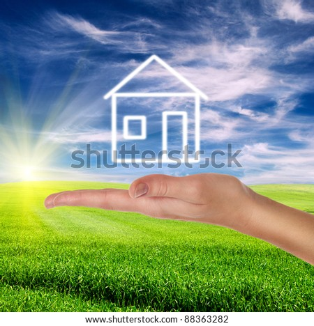 green field over cloudy blue sky with female hand holding white drawn house
