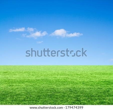 Green field under blue clouds sky.