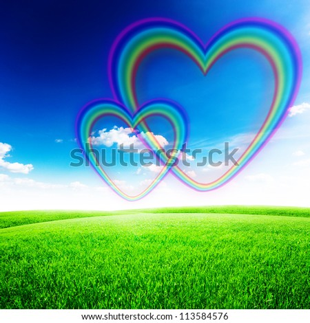 Green field under blue sky with rainbow heart shape on it. Love concept