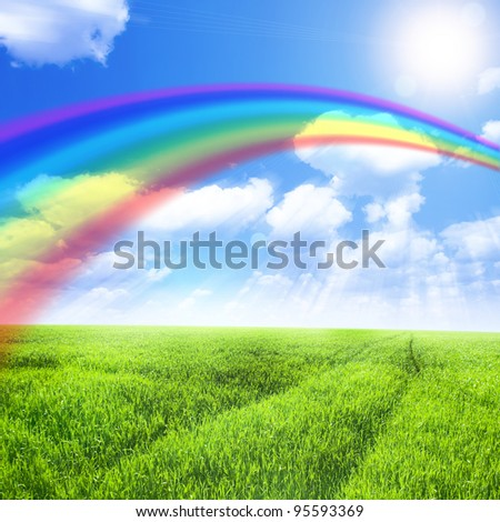 Green field under blue sky with sun and rainbow