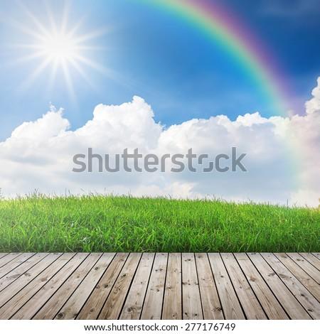Green field under blue sky with sun beam. Wood floor