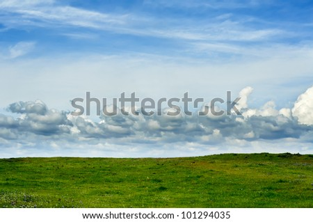 Green Field With Blue Sky and Clouds