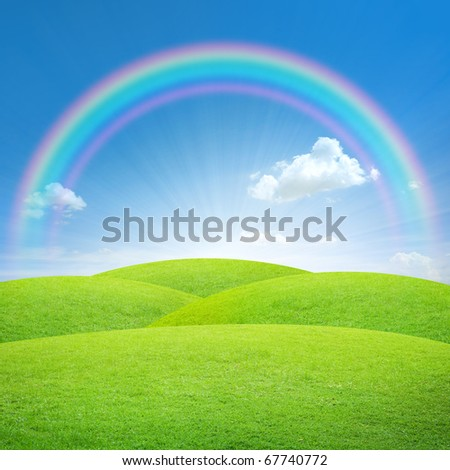 Green field with blue sky and perfect rainbow