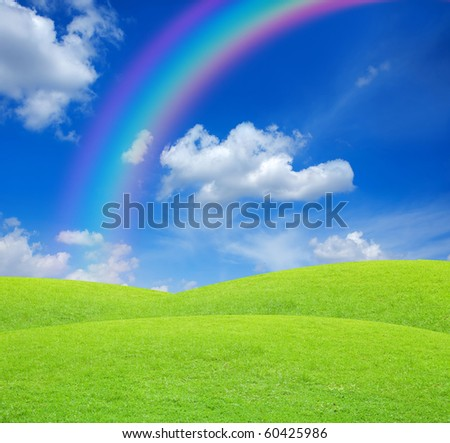 Green field with blue sky and rainbow