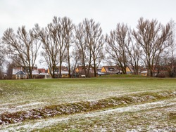 Green field with little snow infront of a block of yellow cottages and hight trees. Late fall, bright colours. Perspective. Noone. Stockholmsvagen, Stockholm