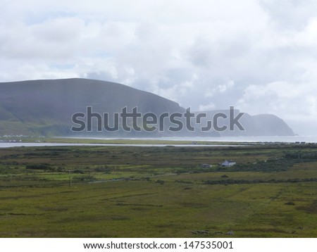 Green fields, misty beach, and looming hills of Achill Island, County Mayo, Ireland