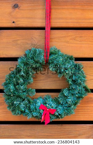 Green fir Christmas wreath with small red bow handing on wooden planks