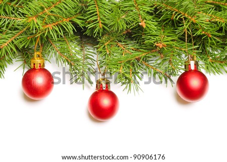 Green fir tree branch with Christmas baubles on white background