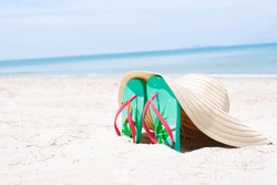 Green flip-flops embroidered on the sand and the hat at the sea with space of blue sky summer holiday and vacation concept.
