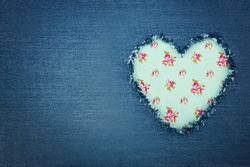 Green floral vintage heart shape for copy space torn from blue denim jeans fabric, romantic love concept background