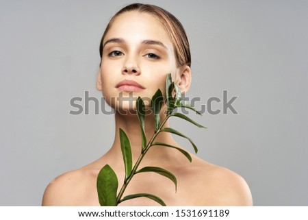 Green flower in the hands of a girl and gray background clean skin #1531691189