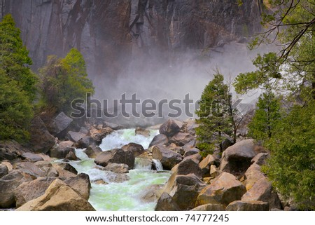Green flowing river over large rocks and boulders with mist and rock cliff in background