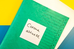 Green Folder with empty sticky note message, text paper note with Corona aktuell means News and Documents. abstract yellow blue paper Background. copy space. blank message text template