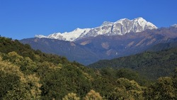 Green forests and snow capped Annapurna range. Landscape in the Himalayas, Nepal.
